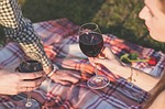 couple having a picnic date drinking a glass of wine