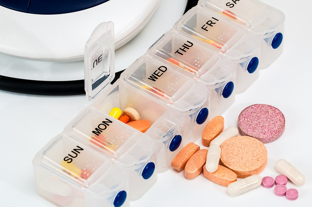 photo of pill organizer with various pills of different shapes and colors