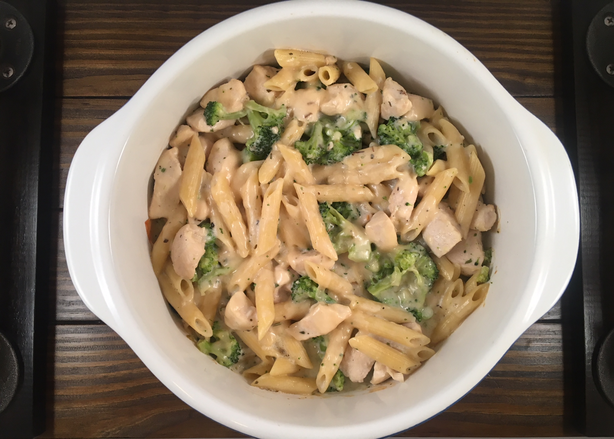 chicken broccoli alfredo in white casserole dish on wooden cutting board