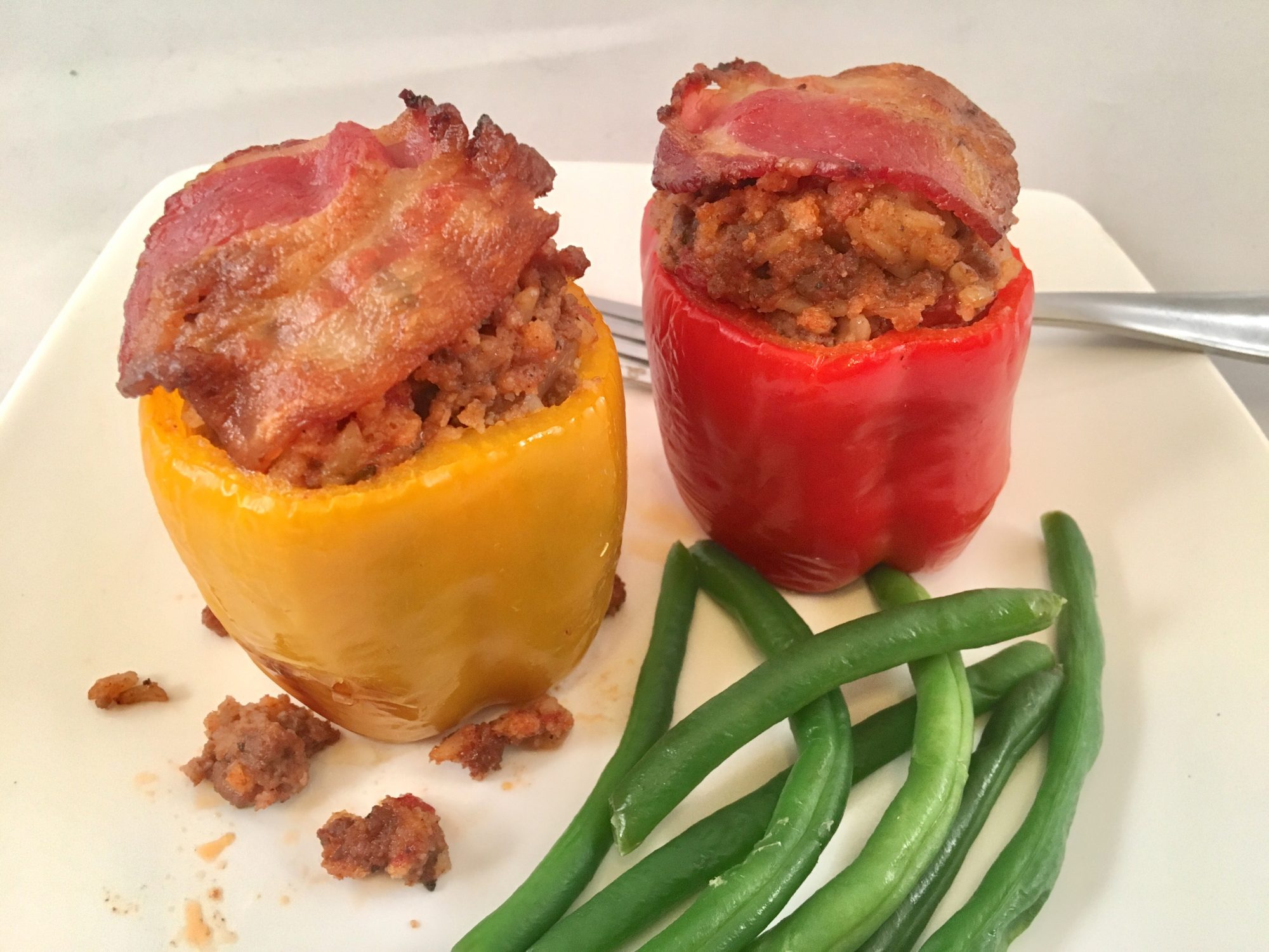 two baked stuffed bell peppers topped with crispy bacon on a white plate with green beans